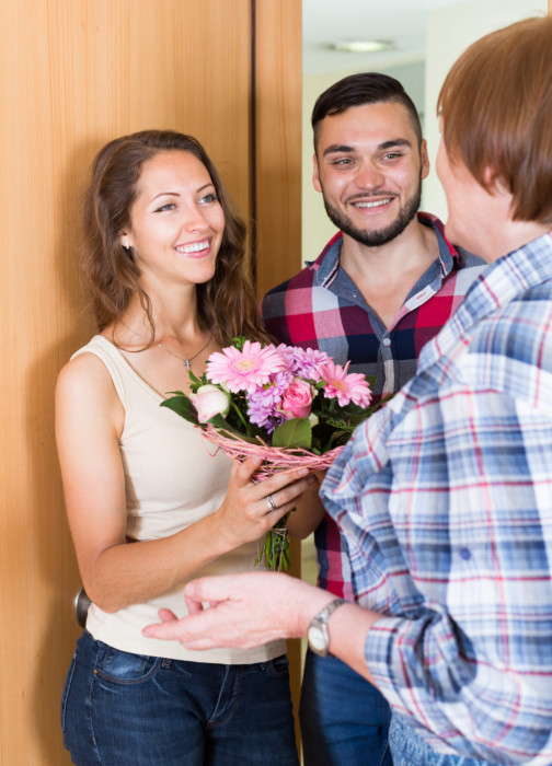 Senior woman meeting smiling young family flowers at the door